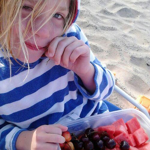 Portrait of girl eating fruit salad at beach