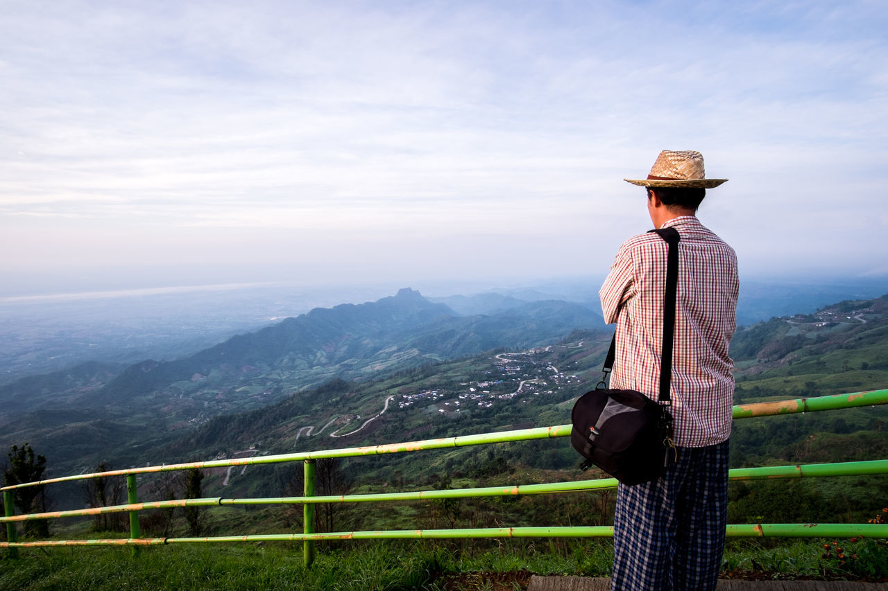 Rear View Of Man Standing By Railing On Mountain Against Cloudy Sky
