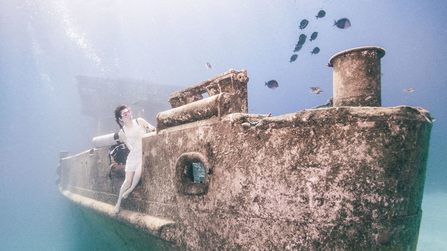 Mid adult woman sitting on shipwreck undersea