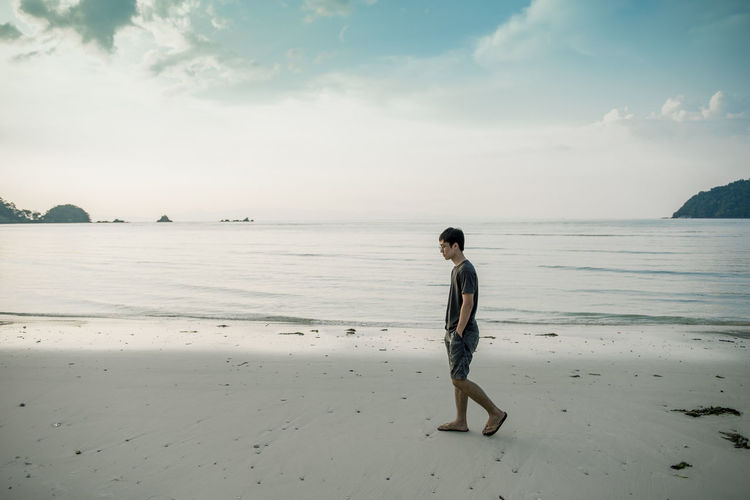 Beach Beauty In Nature Casual Clothing Cloud - Sky Full Length Horizon Over Water Land Leisure Activity Lifestyles One Person Outdoors Real People Sand Scenics - Nature Sea Side View Sky Standing Tranquil Scene Water