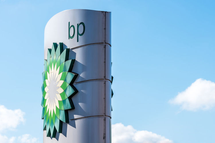 Day view of British Petroleum BP logo BP British Petroleum Gas Architecture Blue Building Exterior Built Structure Cloud - Sky Communication Day Energy Industry Focus On Foreground Green Color Low Angle View Nature No People Oil Outdoors Placard Sign Sky Sunlight Text Western Script White Color
