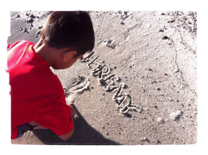 writing his name on the sand Sandwriting LakeToba  Holiday