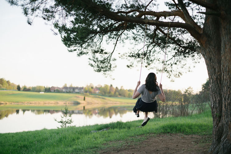 Rear view of woman on swing by lake