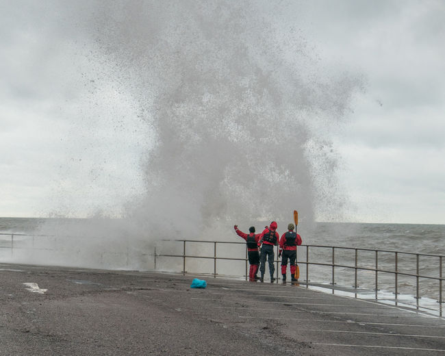 Men looking at large wave crashing on railing