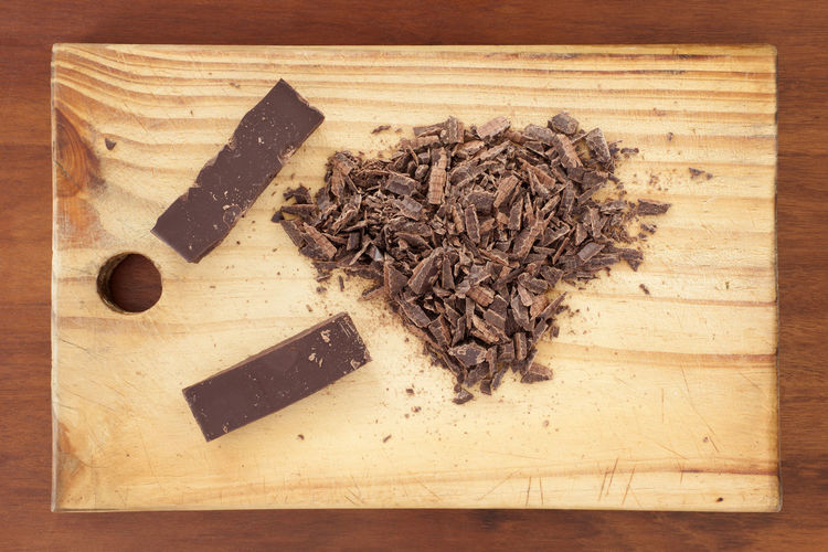 Chopped chocolate.Top view of wooden table with grated chocolate and bars. Baking Brown Brown Color Chocolate Chocolate Bar Chopped Chopped Chocolate Cooking Utensil Cutting Board Directly Above Domestic Kitchen Food And Drink Grated Chocolate Ideas Indoors  Indulgence Kitchen Counter Kitchen Utensils Mama Cutting Board Milk Chocolate Old Cooking Utensils Photography Photoproduction Preparation  Simplicity Studio Shoot Sweet Food Textured  Textured  Wood Wood - Material Wood Grain