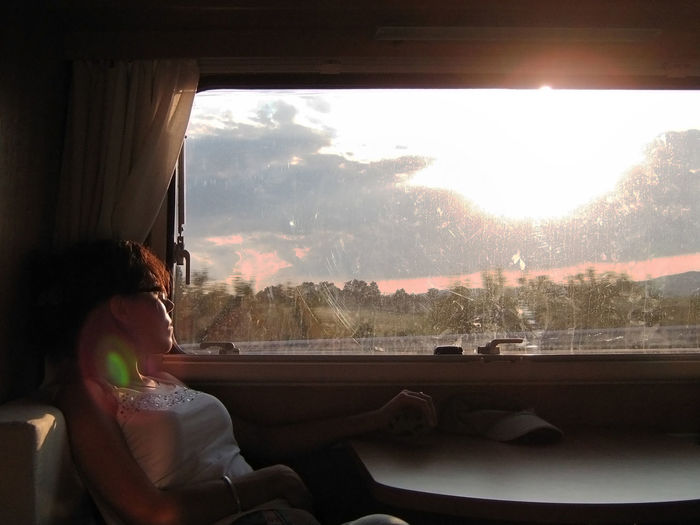View Of Woman Sitting By Window At Sunset