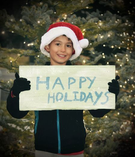 Little Elf Elf Happy Holidays Kids Little Boys Santa's Hat Seasons Colletion Banners And Signs Boy Cheerful Childhood Christmas Christmas Tree Happiness Holding Merry Christmas One Person Outdoors People Santa Helper Seasons Greetings Smiling Standing Text Wearing Santa Hat Young Boy Holding A Sign