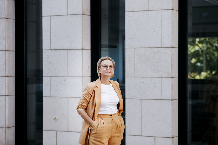 Portrait of smiling woman standing against window