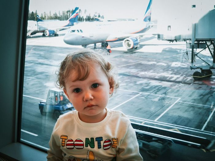 Portrait of cute girl at airport terminal against window