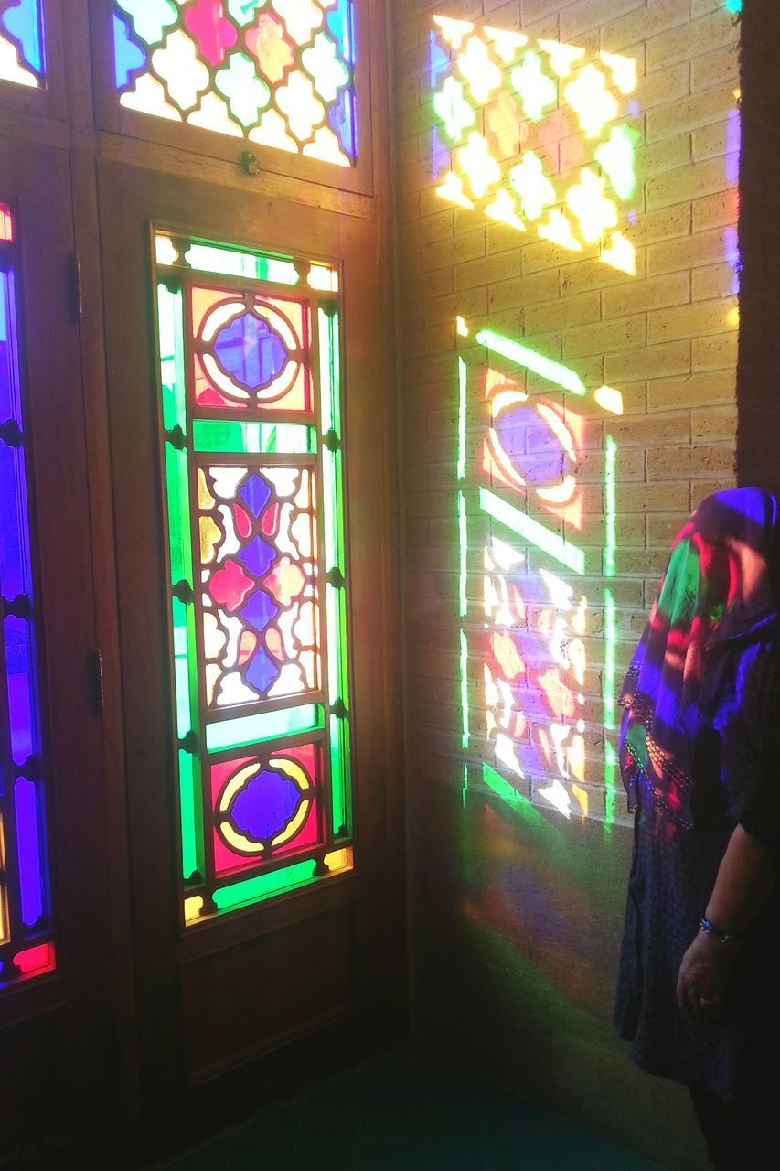 window, multi colored, stained glass, indoors, real people, architecture, glass, one person, day, glass - material, illuminated, built structure, religion, spirituality, sunlight, lifestyles, place of worship, transparent