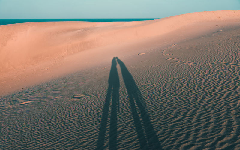 Shadow of couple kissing on sand at beach during sunset