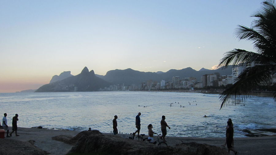 Tourists walking at ipanema beach against mountains during sunset