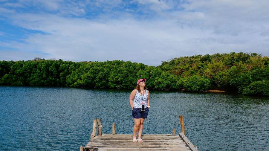 Full Length Of Woman Standing On Pier Over Lake Against Sky
