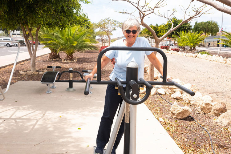 Portrait of senior woman exercising on exercise machine at park