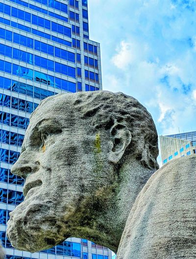 Low angle view of statue against sky in city