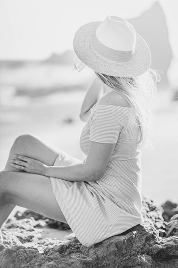 Side view of woman wearing hat sitting on beach