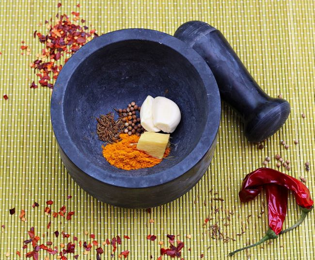 High angle view of various ingredients in mortar by pestle on mat