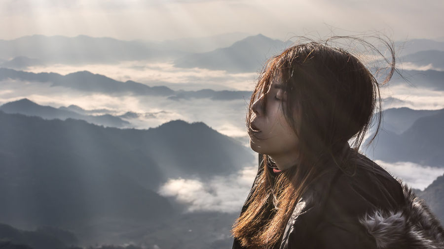 Beauty In Nature Cloud - Sky Contemplation Hair Hairstyle Headshot Leisure Activity Lifestyles Long Hair Mountain Mountain Peak Mountain Range Nature One Person Outdoors Portrait Real People Scenics - Nature Sky Teenager Tranquility Young Adult Young Women