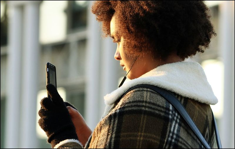 Side View Of Young Woman Holding Mobile Phone