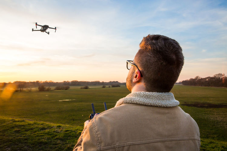 A male drone pilot flying and hovering a drone responsibly with a remote control whilst following the drone code Air Vehicle Sky Airplane Mode Of Transportation Real People Transportation Flying One Person Nature Leisure Activity Headshot Sunset Men Field Rear View Cloud - Sky Portrait Land Environment Drone  Pilot Remote Control Drone Code Hovering In Flight