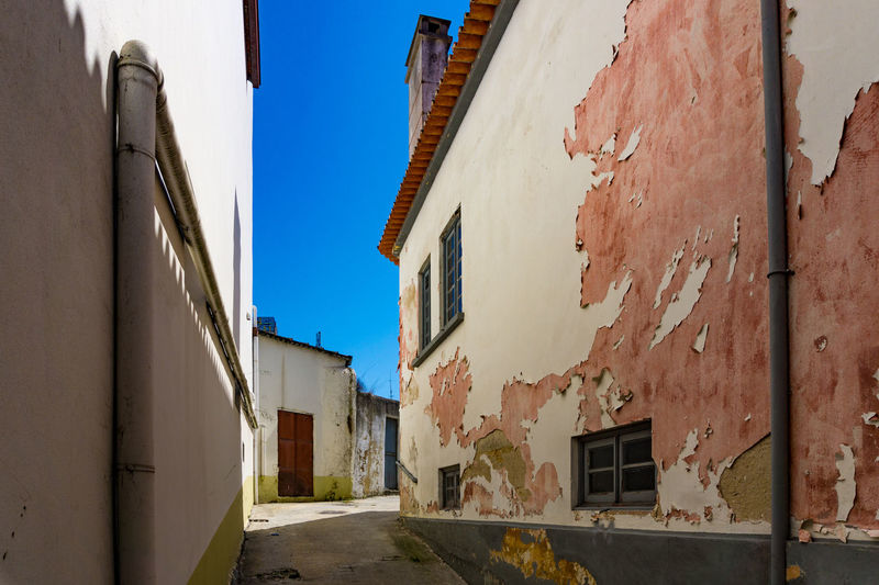 Empty street of residential buildings with peeling render/paint. Aveiro Portugal Architecture Building Exterior Built Structure Day Empty Street Light And Shadow No People Outdoors Patchy Peeling Off Residential Building Sky Summer Window