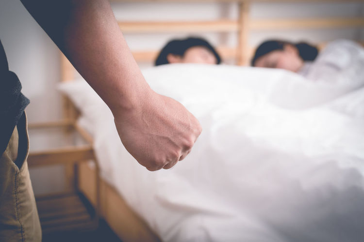 Cropped hand clenching fist against couple sleeping on bed