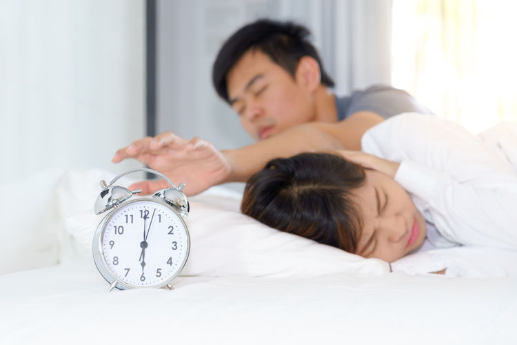 Man Reaching Alarm Clock With Woman On Bed At Home