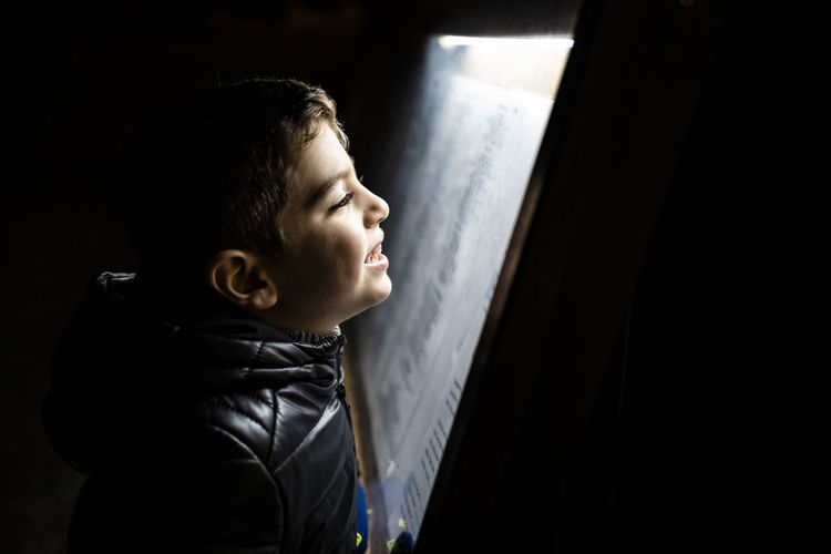 Little boy reading a poster at night