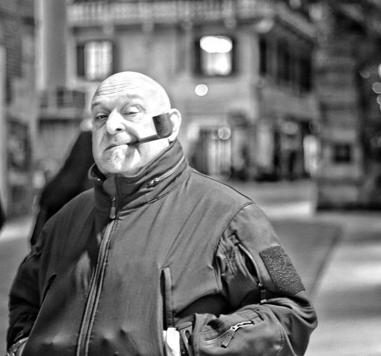 Portrait Of Bald Man Smoking Pipe In City