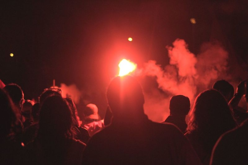 Rear view of protestors watching red distress flare at night