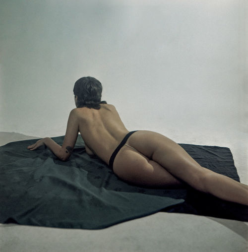 Rear view of woman sitting on bed