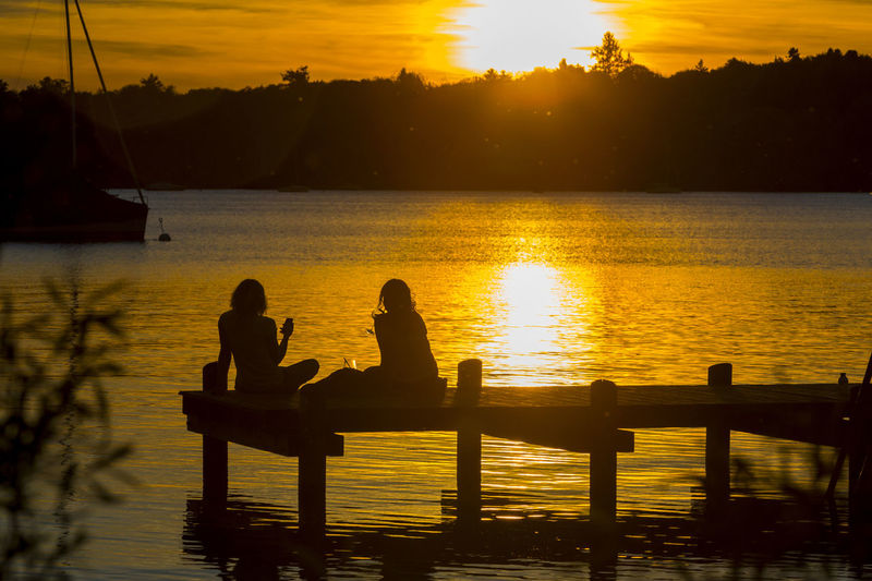 Silhouette female friends resting on jetty over lake during sunset