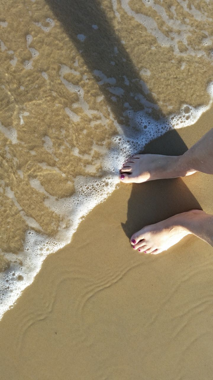 sand, beach, barefoot, shore, low section, shadow, surf, human leg, one person, real people, sunlight, sea, day, water, vacations, human body part, nature, lifestyles, high angle view, wave, summer, leisure activity, outdoors, women, standing, ankle deep in water, human hand, people