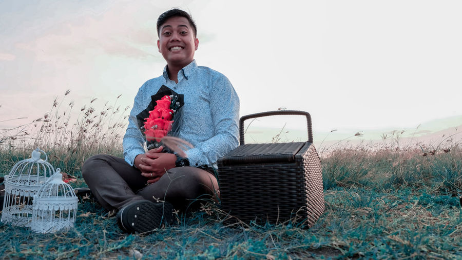 Smiling young man sitting on land against sky