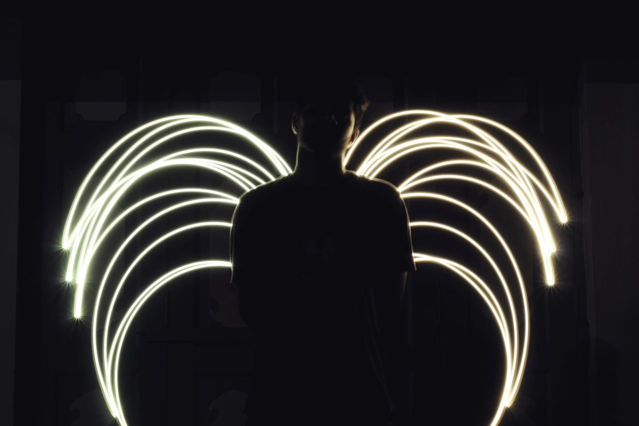 REAR VIEW OF SILHOUETTE PERSON AT ILLUMINATED LIGHT