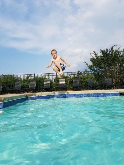 Full length portrait of boy jumping over swimming pool