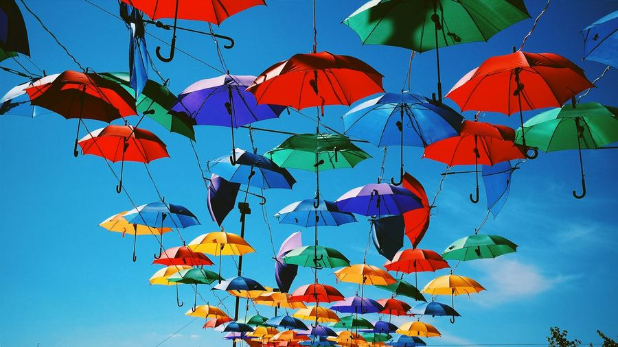 Low angle view of colorful umbrellas hanging on tree against clear sky