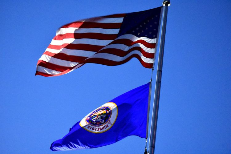 US and MN flag State Flag MN Flag Minnesota EyeEm Selects Patriotism Flag Blue Low Angle View Sky Wind Waving Clear Sky National Icon Pride Star Shape Striped Freedom Outdoors Shape No People Sunlight Day