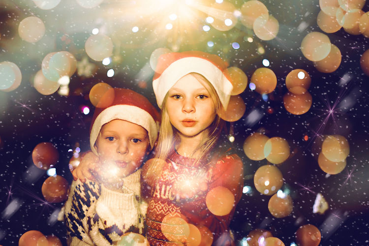 Kids celebrating christmas holiday with sparkler and santa hat
