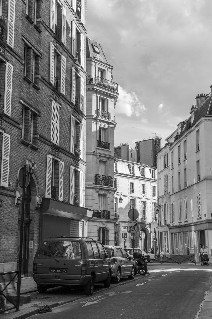 building exterior, architecture, car, built structure, street, transportation, land vehicle, city, mode of transport, sky, road, outdoors, day, no people