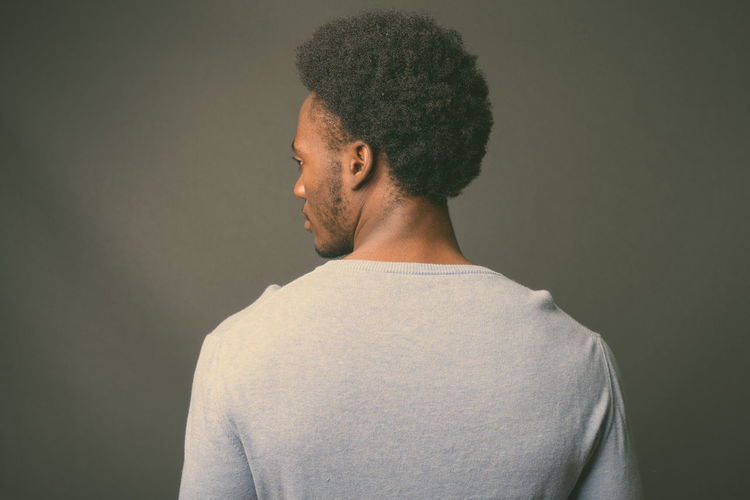 Rear view of man looking away against gray background