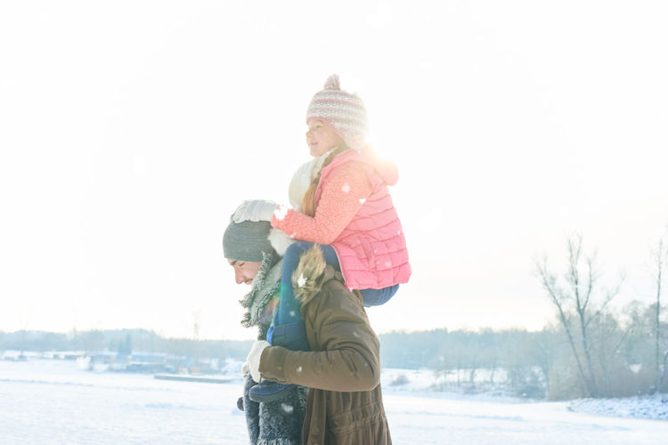 Rear view of mother and daughter against sky during winter