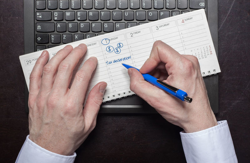 Cropped hands of businessman writing in book on laptop at desk