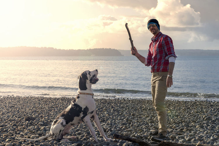 Portrait Of Smiling Mature Man With Dog At Beach Against Cloudy Sky