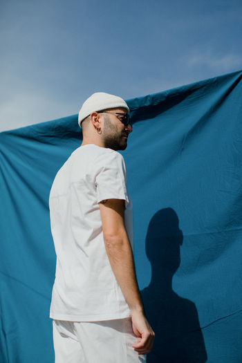 Low angle view of man standing against blue sky