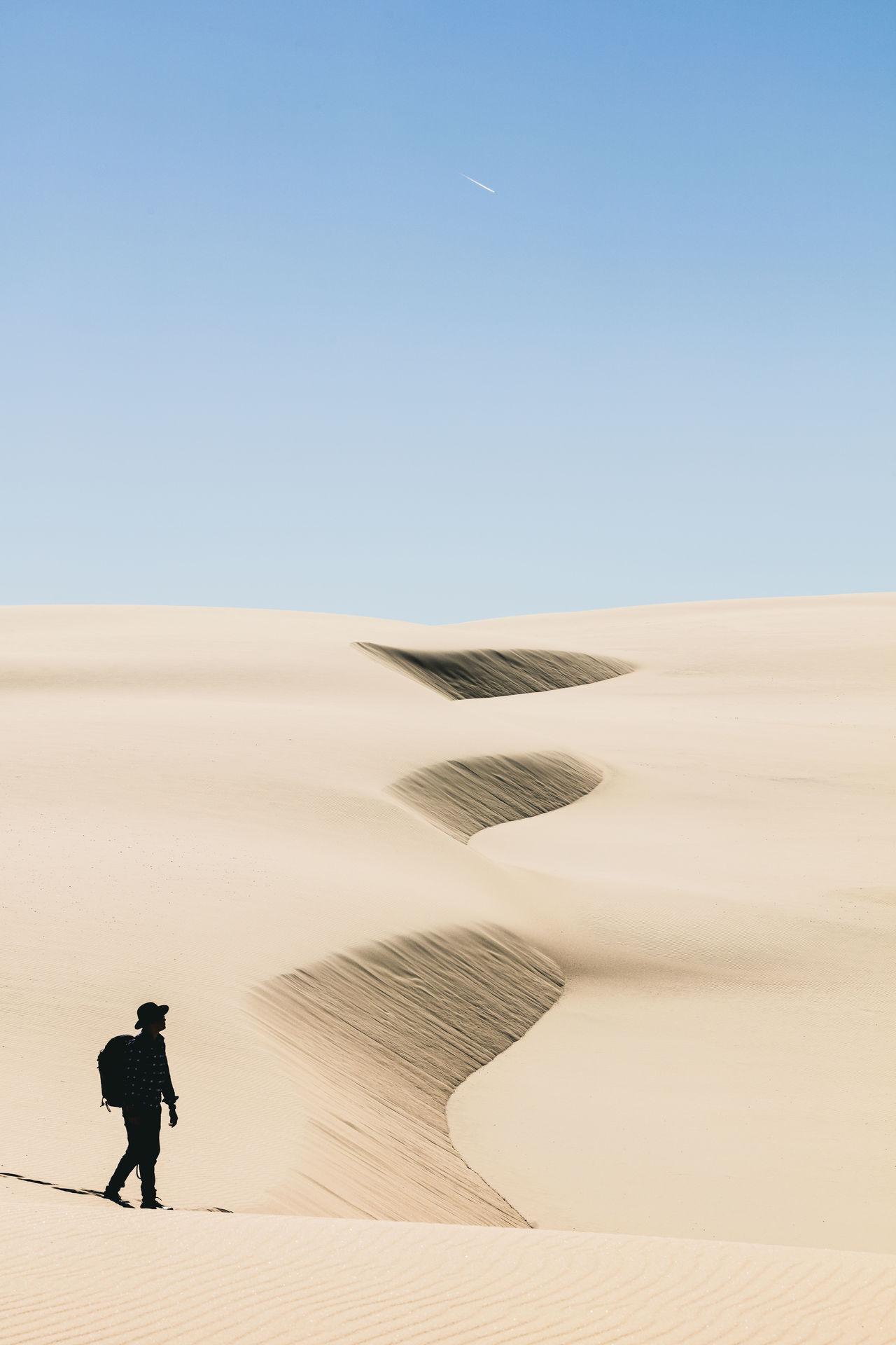 Man walking in desert against clear sky