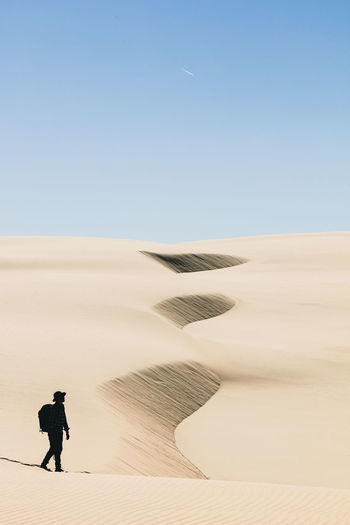 Man Walking In Desert Against Clear Sky