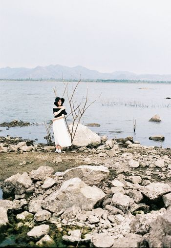 Full length of woman standing against lake and clear sky