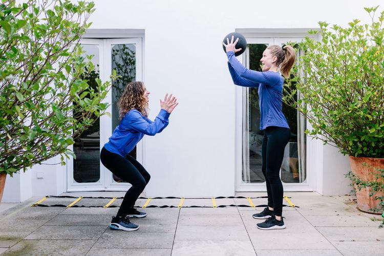 Full length of women standing against plants