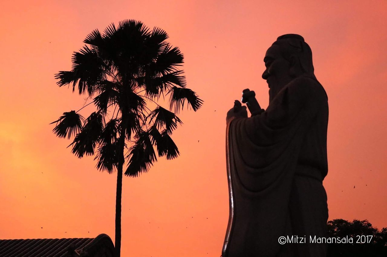 sunset, silhouette, statue, palm tree, human representation, sky, outdoors, men, sculpture, clear sky, nature, beauty in nature, real people, tree, day, people